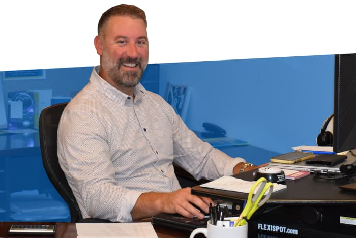 Mike Brenning smiling and working at his desk