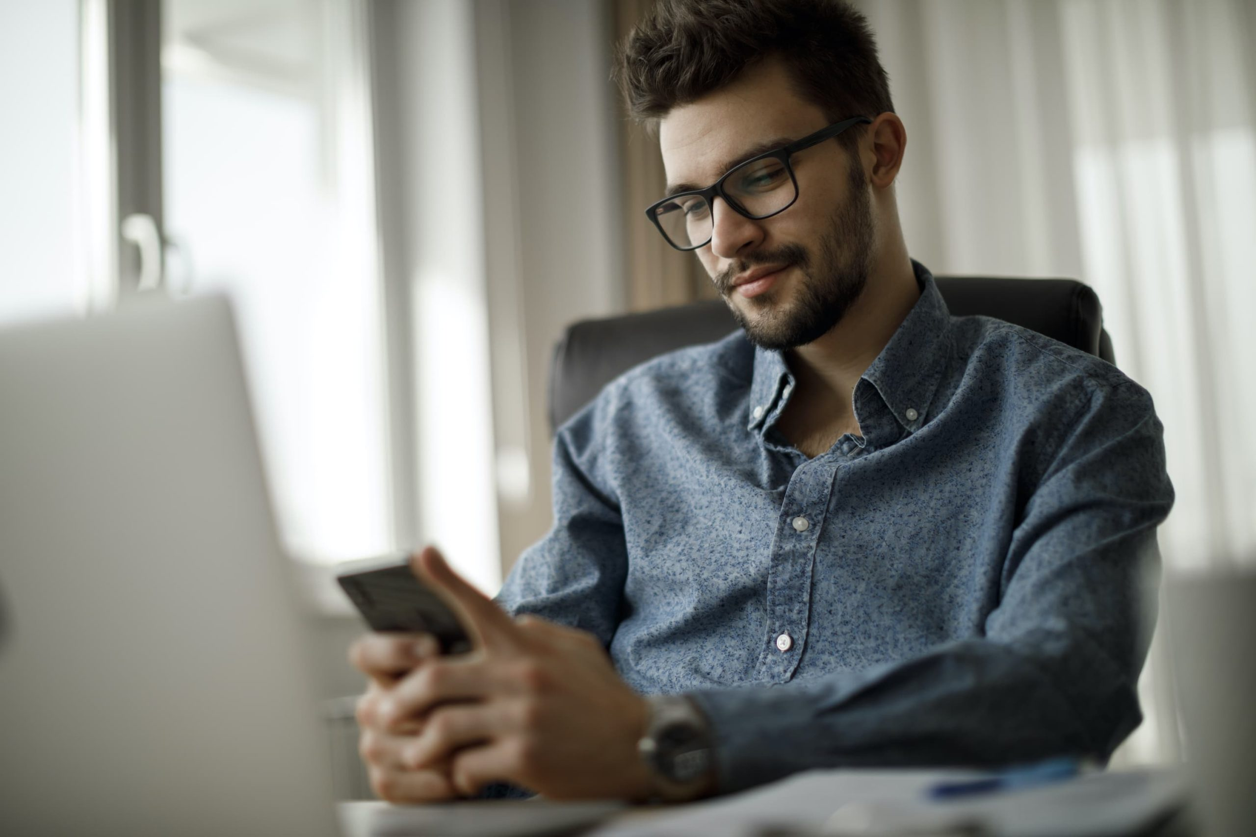 Man texting on cellphone while at desk